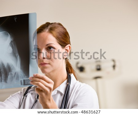 Doctor reviewing x-rays in doctor office - stock photo