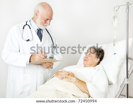 Doctor reviews his hospital patient's medical history, taking notes. - stock photo