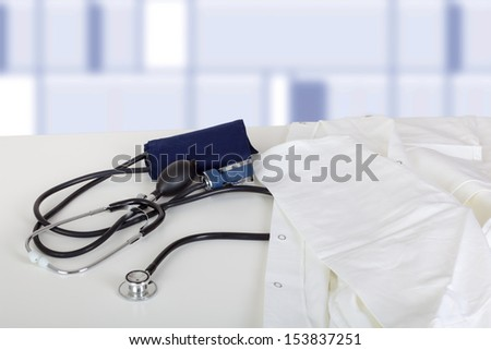 Doctor's coat and stethoscope on the table - stock photo