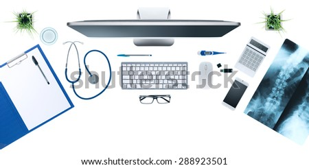 Doctor's desktop with medical equipment, computer and X-ray of human bones on white background, top view - stock photo