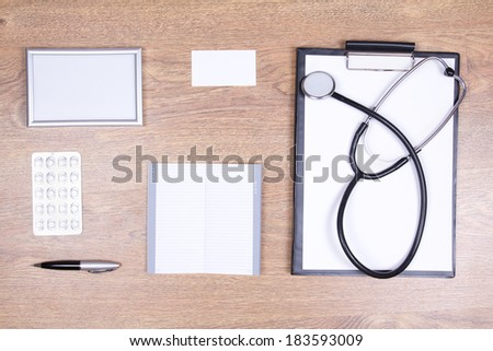 doctor's desktop with stethoscope and office supplies - stock photo