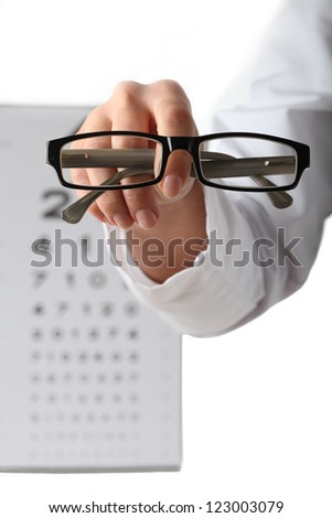 Doctor's hand giving glasses on eye chart background - stock photo