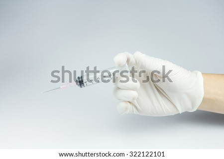 Doctor's hand holding a syringe. - stock photo