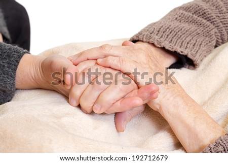 Doctor's hand holding a wrinkled elderly hand - stock photo