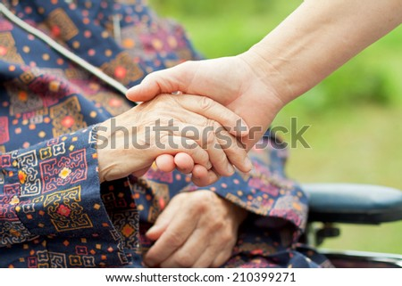 Doctor's hand holding a wrinkled elderly woman's hand. - stock photo