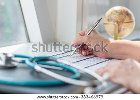 Doctor's hand working using pen writing on patients' medical health record blank paper form with stethoscope on table/ desk: Physician taking note on empty RX paperwork in hospital/ clinic interior  - stock photo