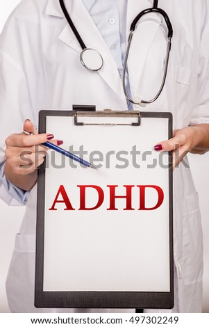 Doctor's hands shows the word ADHD (attention deficit hyperactivity disorder). Medical concept. Detail of a doctor with stethoscope holding a clipboard on white background