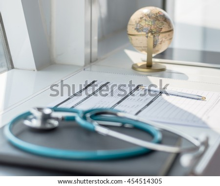 Doctor's notepad work with patient's medical health record blank paper form for prescription with stethoscope on table/ desk: Physician on empty paperwork note pad in hospital/ clinic office interior  - stock photo