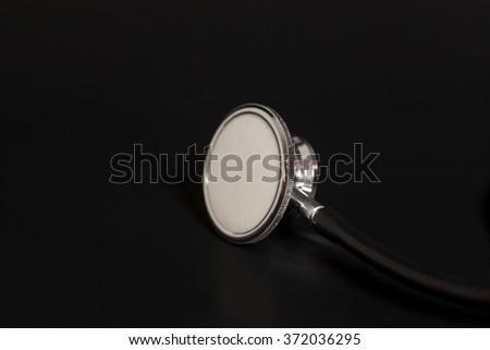 Doctor's stethoscope on black background - stock photo