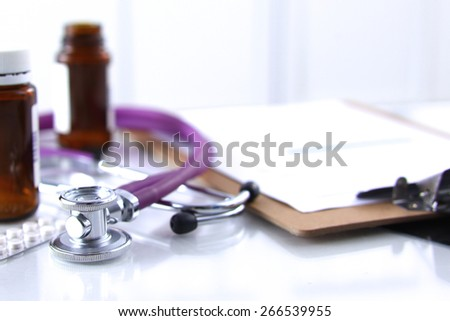 Doctor's stethoscope  with folder and bottle of pills on the desk - stock photo
