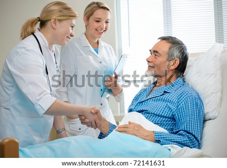 doctor shakes hands with patient in hospital bed
