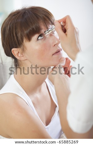 doctor shines a light into eye to check vision ocular health - stock photo