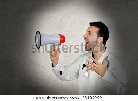 Doctor shouting whit a megaphone on a gray and irregular background - stock photo