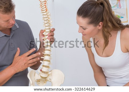 Doctor showing anatomical spine to his patient in medical office - stock photo