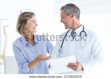 Doctor showing his notes to his patient in medical office - stock photo