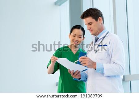 Doctor showing prescription to the nurse - stock photo