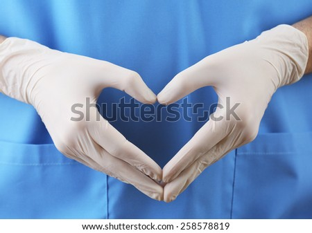 Doctor showing shape of heart by his hands in sterile gloves, closeup view - stock photo