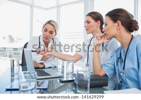 Doctor showing something on a laptop to her colleagues during a meeting room - stock photo