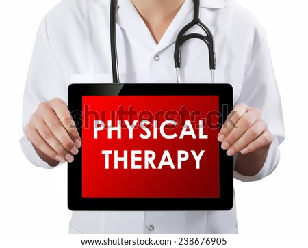 Doctor showing tablet with PHYSICAL THERAPY text.  - stock photo