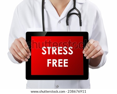 Doctor showing tablet with STRESS FREE text.  - stock photo