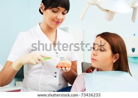 doctor showing to patient how cleaning teeth