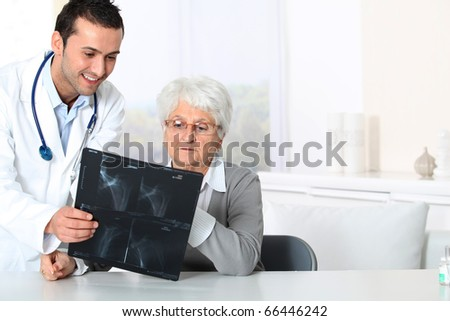 Doctor showing x-ray results to elderly woman - stock photo