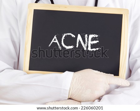 Doctor shows information on blackboard: acne - stock photo