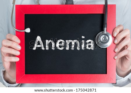 Doctor shows information on blackboard: anemia - stock photo