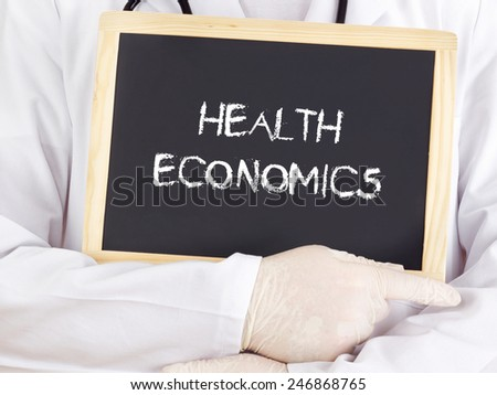 Doctor shows information on blackboard: health economics - stock photo