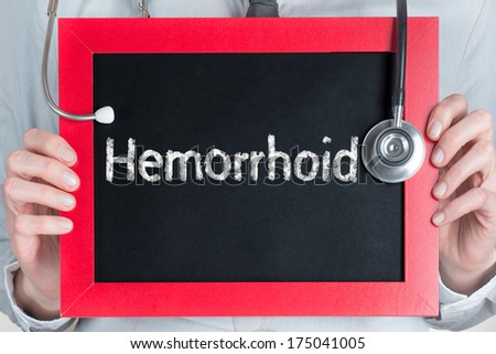 Doctor shows information on blackboard: hemorrhoid  - stock photo