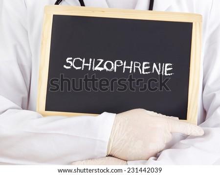 Doctor shows information: Schizophrenia in german language - stock photo