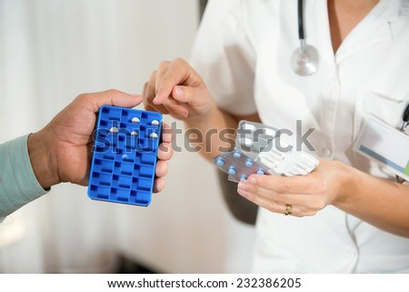 Doctor shows the patient how to use daily dose pills - stock photo
