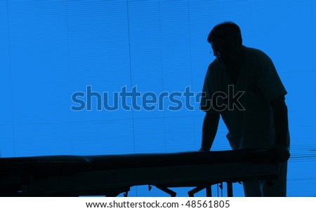 Doctor silhouette with an hospital bed at a hospital - stock photo