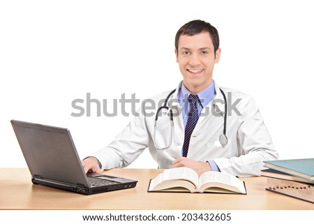 Doctor sitting at a desk and working on laptop isolated on white background - stock photo