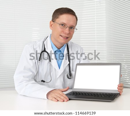 Doctor sitting at his desk with laptop computer - stock photo