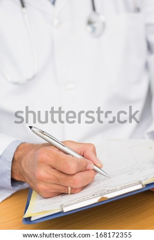 Doctor sitting at his desk writing on clipboard in his office at the hospital