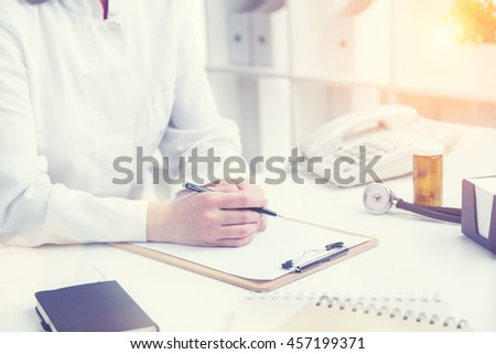 Doctor sitting at table ready to make notes, only hands seen. Office. Concept of work. Toning image