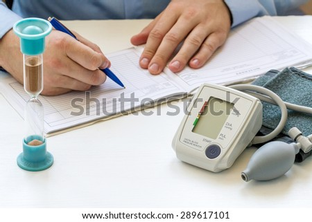 Doctor sitting at the white table with digital blood pressure monitor and hourglass and writing a prescription - stock photo