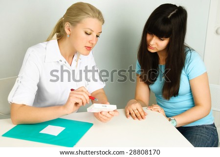doctor sitting by the table and consulting a patient in her office