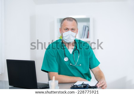 Doctor sitting in his office with a mask - stock photo