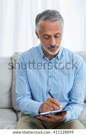 Doctor sitting with a clipboard on sofa