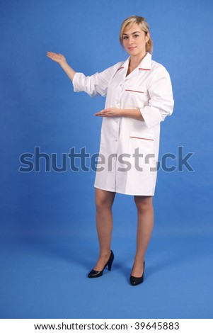Doctor smiling, pointing to her right with both hands - stock photo