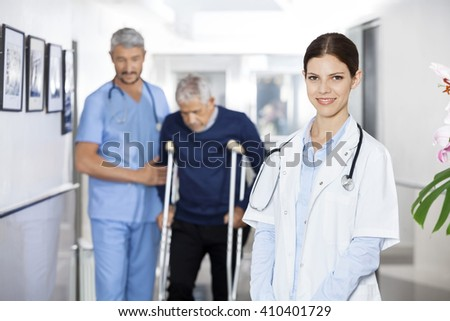 Doctor Smiling While Colleague Assisting Senior Man With Crutche - stock photo