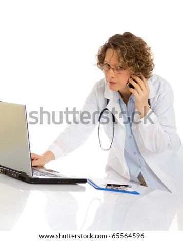 Doctor speaks by cellphone and work a laptop - stock photo