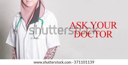 Doctor Standing front of Wall written ASK YOUR DOCTOR - stock photo
