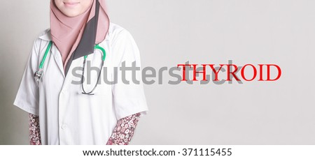 Doctor Standing front of Wall written THYROID - stock photo