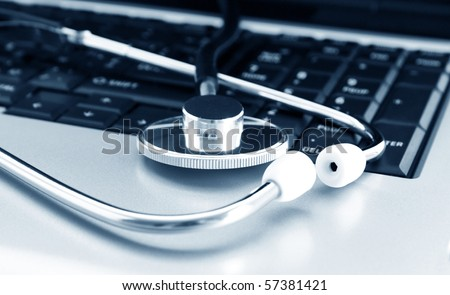 Doctor stethoscope on the laptop keyboard. Image in blue tone