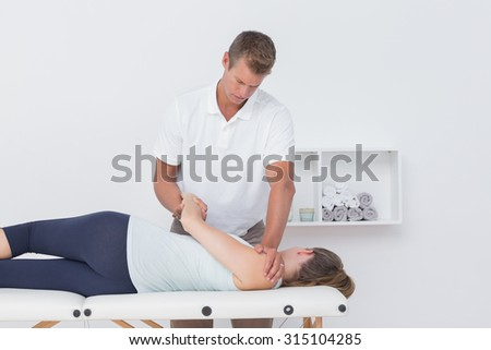 Doctor stretching a woman back in medical office - stock photo