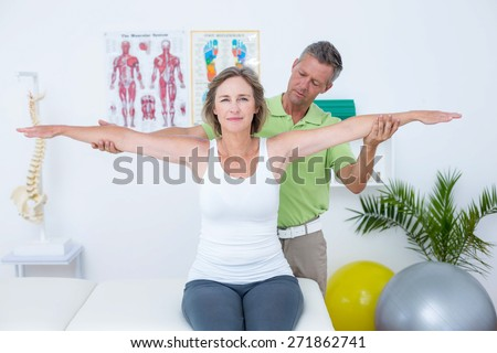 Doctor stretching his patients arms in medical office - stock photo