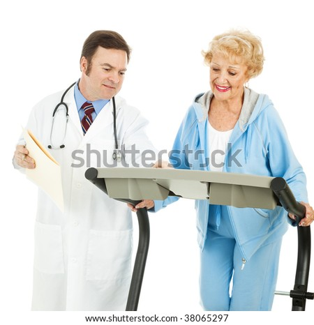 Doctor supervising a fit senior woman as she works out on a treadmill.  Isolated on white. - stock photo